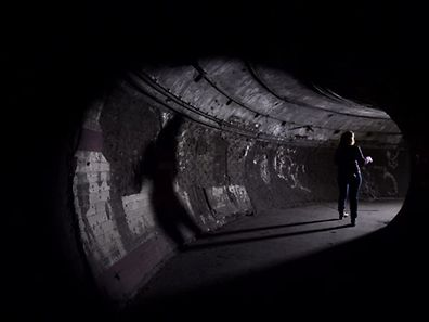 A visitor walks through a tunnel in the disused Down Street London Underground tube station in London