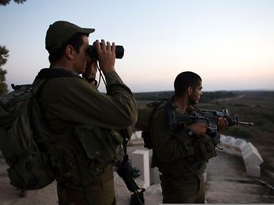 Israeli soldiers stand near the border with the Gaza Strip July 26