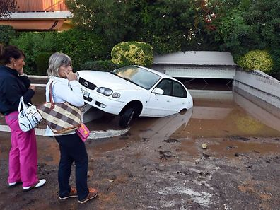 People stand next to a damaged car after violent storms and floods on October 4, 2015, in Mandelieu-la-Napoule, southeastern France. Violent storms and flooding along the French riviera killed 13 people by early Sunday, emergency responders and local officials said, including three who drowned in a retirement home inundated when a river broke its banks. AFP PHOTO / BORIS HORVAT