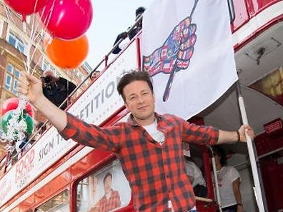British Chef and television presenter Jamie Oliver gestures during an interview while visiting a North London school in London to promote Food Revolution Day on May 15, 2015. Jamie Oliver is calling for a global campaign to put compulsory practical food eduction on the school curriculum of the G20 countries. AFP PHOTO / LEON NEAL