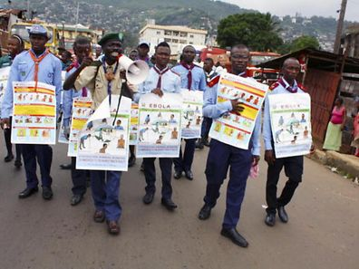 Members of a UNICEF supported social mobilization team walk on a street carrying posters with information on the symptoms of Ebola virus disease (EVD)