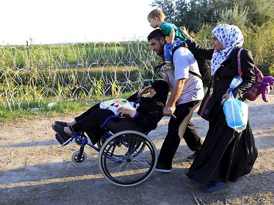 Refugees from Syria walk along a road in Hugary after crossing over from Serbia