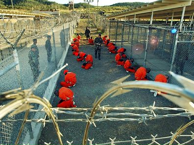 In this photo released 18 January 2002 by the Department of Defense, Al-Qaeda and Taliban detainees in orange jumpsuits sit in a holding area under the surveillence of US military police at Camp X-Ray at Naval Base Guantanamo Bay, Cuba, during in-processing to the temporary detention facility 11 January 2002.  The detainees, captured in Afghanistan during Operation Enduring Freedom, are given a basic physical exam by a doctor, to include a chest x-ray blood samples drawn to assess their health.  AFP PHOTO / US NAVY / Shane T. McCOY ORG XMIT: GTB06