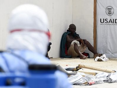 A newly arrived patient suspected of suffering from the Ebola virus sits on the ground at Island Hospital in Monrovia, Liberia