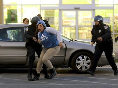 """Baltimore police officers chase down, tackle and arrest a woman after she and other looters ran from a """"Deals"""" store (rear) with merchandise during clashes between rioters and police after the funeral of Freddie Gray in Baltimore, Maryland April 27, 2015. Baltimore erupted in violence on Monday as hundreds of rioters looted stores, burned buildings and injured at least 15 police officers following the funeral of a 25-year-old black man who died after he was injured in police custody. REUTERS/Jim Bourg"""