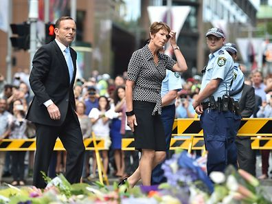 Prime Minister Tony Abbott and his wife Margaret arrive to pay respects and lay wreaths at a makeshift memorial near the scene of a fatal siege in the heart of Sydney's financial district on December 16, 2014.