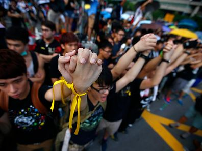 Protesters hold their hands as they gather around the Golden Bauhinia Square during an official flag raising ceremony to commemorate the Chinese National Day in Hong Kong, October 1, 2014.