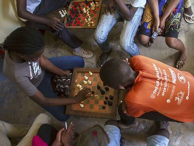 18-year-old Phiona Mutesi (L) plays a game of chess with her colleagues at the chess academy in Kibuye, Kampala, on January 26, 2015.