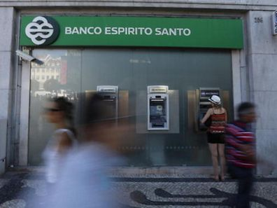 People pass near an office of Portuguese bank Banco Espirito Santo in Lisbon