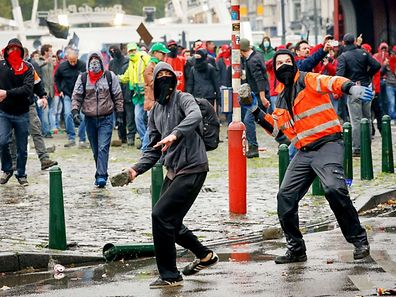 Demonstrators prepare to throw rocks towards police officers following an anti-austerity demonstration in Brussels on October 7, 2015.    Tens of thousands of Belgian protesters took to the streets of Brussels to rally against austerity measures introduced by the government of Prime Minister Charles Michel, police and trade unions said. Brussels police said 81,000 demonstrators turned out while the main union organising the protest put the number at 100,000, making it one of the biggest rallies of its kind in Belgium in recent years.  AFP PHOTO / BELGA / THIERRY ROGE
