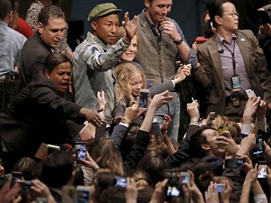 "Musician Pharrell Williams waves to youth gathered in the United Nations General Assembly hall on the occasion of the International Day of Happiness on the theme ""Young People in Support of Climate Action"" at U.N. headquarters in New York, March 20, 2015. REUTERS/Mike Segar"