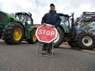 A French farmer holds a stop road sign as he blocks trucks that transport food goods coming from foreign countries at the French German border in Strasbourg