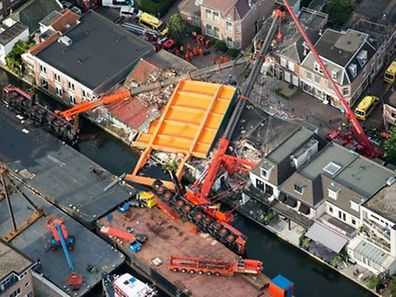 An aerial picture taken on August 3, 2015 shows the two cranes that have fallen onto houses in Alphen aan den Rijn. About 20 people were injured in the western Dutch town of Alphen aan den Rijn when two cranes working on a bridge upgrade toppled onto houses nearby, the fire brigade said. AFP PHOTO / ANP /  BRAM VAN DE BIEZEN    ***NETHERLANDS OUT***