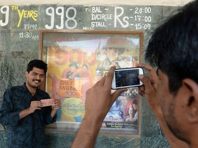 "Indian cinemagoer Gaurav Kulkarni (L) gets a souvenir photo taken with his ticket before a screening of the popular Bollywood Hindi film ""Dilwale Dulhania Le Jayenge"" at the Maratha Mandir movie theatre in Mumbai."