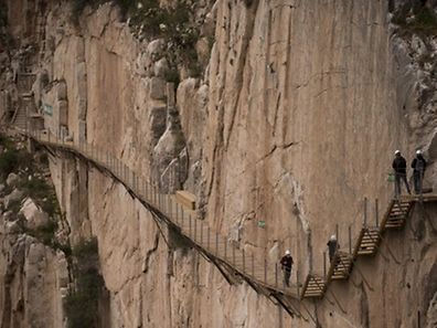 "Journalists walk during a visit to the foot-path ""El Caminito del Rey"" (King's little path) a narrow walkway hanging and carved on the steep walls of a defile in Ardales near Malaga on March 15, 2015. The one meter wide and 7.7 km long path, hanging from Ardales' defile at 100 meter high, was closed in the mid 90's after several hikers resulted dead when walking it. Once restored it will be reopened to the public on March 28, 2015.   AFP PHOTO/ JORGE GUERRERO"
