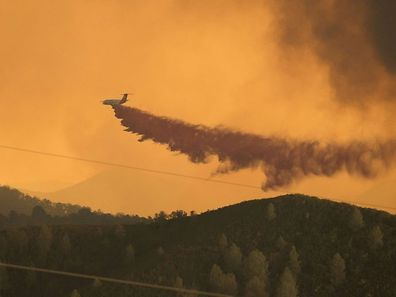 An air tanker drops fire retardant along a burning ridge as fire personnel battle the Rocky fire near South Lake, California on August 1, 2015. Thousands of firefighters were battling nearly two dozen blazes across drought-parched California, while at least two of the infernos shut down miles of highway traffic, authorities and media said.  AFP PHOTO/JOSH EDELSON