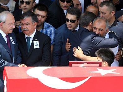 Le Premier ministre turc Ahmet Davutoglu (2e à dr.) embrasse le père du soldat turc Hamza Yildirim, tué par une attaque du PKK.