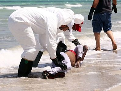 Members of the Libyan Red Crescent, wearing protective white clothing and masks, collect the body of a migrant that had washed ashore on a beach on August 28, 2015 in the port town of Zuwara, about 160 kms West of Tripoli, after two boats carrying hundreds of migrants and refugees sank off the coast of the town. Seddik Said, head of a joint crisis team, told AFP at the scene that according to survivors around 400 people were on board the main vessel and another 60 on a smaller boat which sank on August 26. At least 76 people have died.   AFP PHOTO / MAHMUD TURKIA