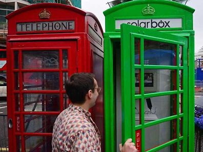 The first traditional London telephone box (R) to be transformed into a solar-powered mobile phone charger for use by the public