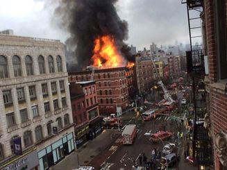 Fire shoots from the roof of a building after it collapsed and burst into flames in New York City's East Village as seen in this picture taken by Scott Westerfeld March 26, 2015.  Rescuers from the Fire Department of New York (FDNY) were headed to the location, which was on Second Avenue and East 7th Street in Manhattan, an FDNY spokeswoman said.   REUTERS/Scott Westerfeld  ATTENTION EDITORS - THIS PICTURE WAS PROVIDED BY A THIRD PARTY. REUTERS IS UNABLE TO INDEPENDENTLY VERIFY THE AUTHENTICITY, CONTENT, LOCATION OR DATE OF THIS IMAGE. FOR EDITORIAL USE ONLY. NOT FOR SALE FOR MARKETING OR ADVERTISING CAMPAIGNS.  NO SALES. NO ARCHIVES.