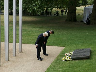London Mayor Boris Johnson (l) and Britain's Prime Minister David Cameron bow after laying wreaths at the memorial to victims of the July 7, 2005 London bombings, in Hyde Park