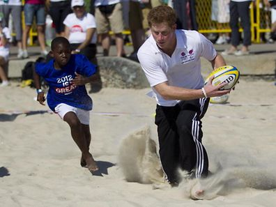 File photo of Britain's Prince Harry playing rugby with kids at Flamengo's beach in Rio de Janeiro, Brazil in 2012.