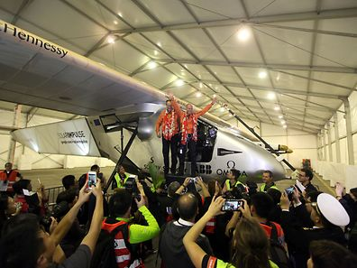 Swiss pilots Andre Borschberg (L) and Bertrand Piccard (R) of Solar Impulse 2, wave to the media after landing in Chongqing airport at 1:35 am (17:35 GMT Monday) after a 22-and-a-half hour flight from Myanmar, on March 31, 2015. Solar Impulse 2 landed in China, the world's biggest carbon emitter, as it completed the fifth leg of its landmark circumnavigation of the globe powered solely by the sun.     CHINA OUT      AFP PHOTO