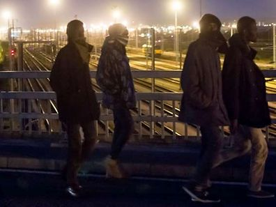 Migrants cross a bridge over the railway tracks of the Eurotunnel terminal on July 28