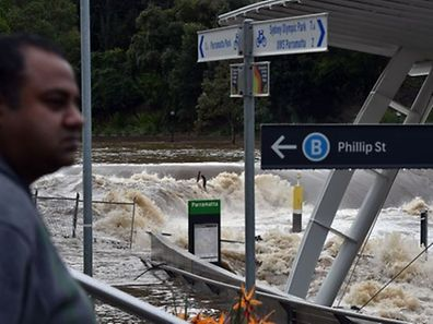 A resident looks at the over-flowing Parramatta river at the flooded Parramatta ferry wharf in Sydney on April 22, 2015.