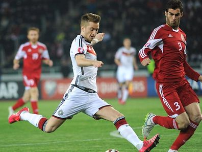 Germany's midfielder Marco Reus (C) kicks the ball next to Georgia's defender Solomon Kverkvelia during the Euro 2016 qualifying football match between Georgia and Germany in Tbilisi on March 29, 2015. AFP PHOTO / VANO SHLAMOV