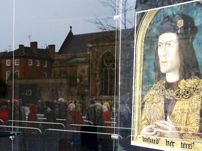 Members of the public are reflected in a shop window as they queue to view the coffin of King Richard III at Leicester Cathedral, central England, March 25, 2015.  King Richard III, the medieval English monarch whose remains were found under a car park three years ago, will be reburied on March 26, nearly 530 years after he was slain in battle.  REUTERS/Darren Staples