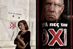 """TOPSHOTS A woman passes by the headquarters of Bank of Greece daubed with the word """"NO"""" and a poster with a portrait of German Finance Minister Wolfgang Schaeuble that reads """" Now tell him NO """" ahead of a referendum in Athens, on July 3, 2015. Greece's government and international creditors raised the stakes on July 2 over a weekend referendum seen as decisive for the nearly insolvent EU country's political and financial future. While Prime Minister Alexis Tsipras has urged Greeks to vote 'No' to the austerity measures demanded by international creditors, opposition parties including the centre-right New Democracy are campaigning for a 'Yes' vote in the referendum on July 5.  AFP PHOTO / ARIS MESSINIS"""
