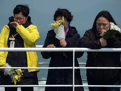 Relatives of victims of the South Korean ferry disaster stand on the deck of a boat during a visit to the site of the sunken ferry