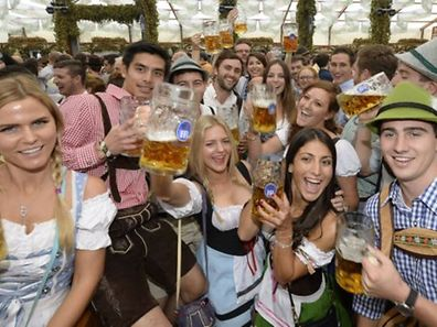 Visitors celebrate with first beer mugs the opening of the traditional Bavarian Oktoberfest festival at the Theresienwiese in Munich, southern Germany, on September 20, 2014.