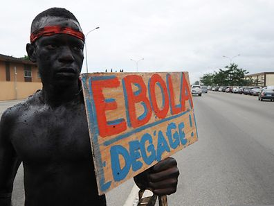 """A man holds a placard reading """"Ebola, go away"""" as members of the artist group """"'Be Kok Spirit'' march to raise awareness on the Ebola virus in Abidjian, Ivory Coast"""