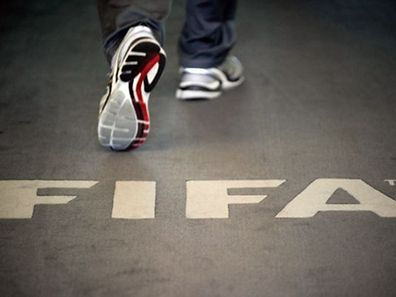 (FILES) This file photo taken on September 3, 2013 shows a man walking past the logo of the FIFA (Federation Internationale de Football Association) inside the organisation's headquarters in Zurich.  Top FIFA officials were arrested early on May 27, 2015 by Swiss police acting on US corruption charges, The New York Times reported.    AFP PHOTO / FILES / SEBASTIEN BOZON