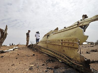 A French soldier and a journalist look at debris of the Air Algerie Flight AH 5017 scattered at the crash site in Mali's Gossi region, west of Gao