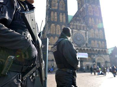 Polizisten patrouillieren am Samstag in der Innenstadt von Bremen, im Hintergrund der Dom.