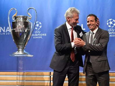 Former players Germany's Paul Breitner (L), representing Bayern Munich and France's Ludovic Giuly, representing Barcelona, react on stage after the draw for the UEFA Champions League semi-final football matches at the UEFA headquarters in Nyon on April 24, 2015. AFP PHOTO / FABRICE COFFRINI