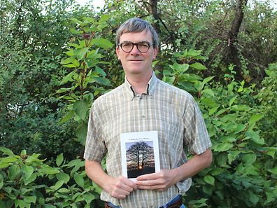 "Terry Adams holds up his new book, ""A Sunny Day Near Mexico with Poems from Home"""