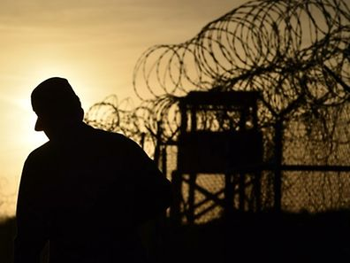 "(FILES) This April 9, 2014 file photo made during an escorted visit and reviewed by the US military, shows an US soldier walking next to the razor wire-topped fence at the abandoned ""Camp X-Ray"" detention facility at the US Naval Station in Guantanamo Bay, Cuba.  A US court has ordered former Guantanamo detainee Omar Khadr to pay USD 134.2 million in compensation over a 2002 grenade attack that killed two US soldiers in Afghanistan, the victims' lawyer said July 2, 2014.  AFP PHOTO/ MLADEN ANTONOV"