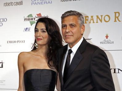 Director and actor George Clooney arrives with his fiancee barrister Amal Alamuddin to attend the Celebrity Fight Night event in Florence September 7, 2014