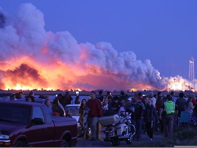 People who came to watch the launch walk away after an unmanned rocket owned by Orbital Sciences Corporation exploded (background) October 28, 2014 just seconds after lift-off from Wallops Island, Virginia