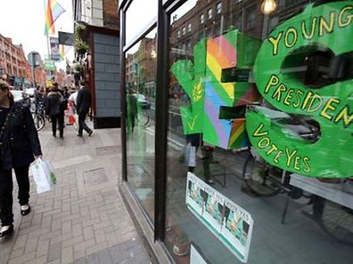 A woman wals past a pro same-sex marriage 'Yes' banner hanging in the window the Green Party's office in Dublin on May 21, 2015. Ireland goes to the polls tomorrow to vote on whether same-sex marriage should be legal, in a referendum that has exposed sharp divisions between communities in this traditionally Catholic nation.     AFP PHOTO / PAUL FAITH