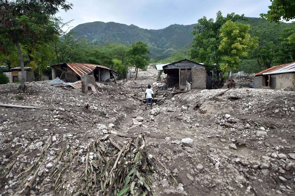 August 29, 2015, a boy walking past houses destroyed by a mudslide caused by the rains from Tropical Storm Erika in Montrouis, Haiti.