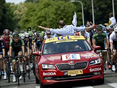 General director of the Tour de France, Christian Prudhomme, gestures to announce that the race is neutralised after a big crash of cyclists at the head of the pack during the 159.5 km third stage of the 102nd edition of the Tour de France cycling race on July 6, 2015, between the belgian cities of Antwerp and Huy.  AFP PHOTO / ERIC FEFERBERG