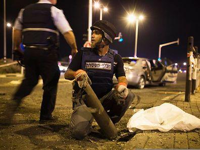 Ein israelischer Polizist untersucht die Reste einer Rakete, die von Gaza aus abgefeuert wurde.