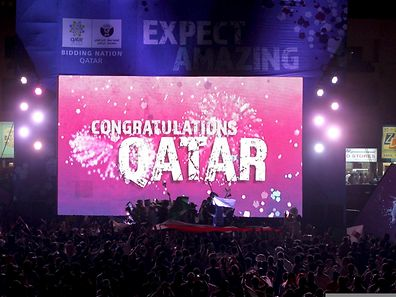 "People celebrate in front of a screen that reads ""Congratulations Qatar"" after FIFA announced that Qatar will be host of the 2022 World Cup in Souq Waqif in Doha"