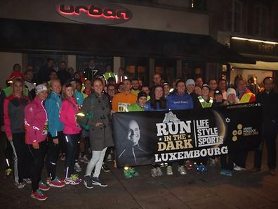 Finishers of the first Luxembourg Run in the Dark pose for a photo outside Urban