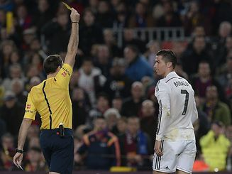 """The referee gives a yellow card to Real Madrid's Portuguese forward Cristiano Ronaldo (R) during the """"clasico"""" Spanish league football match FC Barcelona vs Real Madrid CF at the Camp Nou stadium in Barcelona on March 22, 2015.   AFP PHOTO/ JOSEP LAGO"""